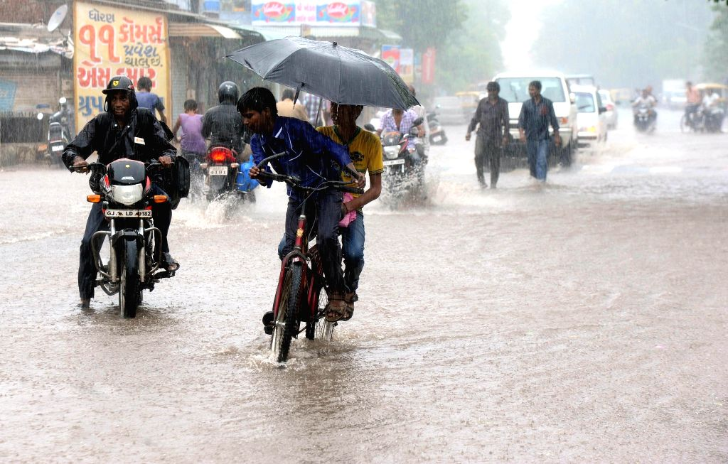 Vehicles wade through a flooded road after a heavy shower in Ahmedabad on July 24, 2014.