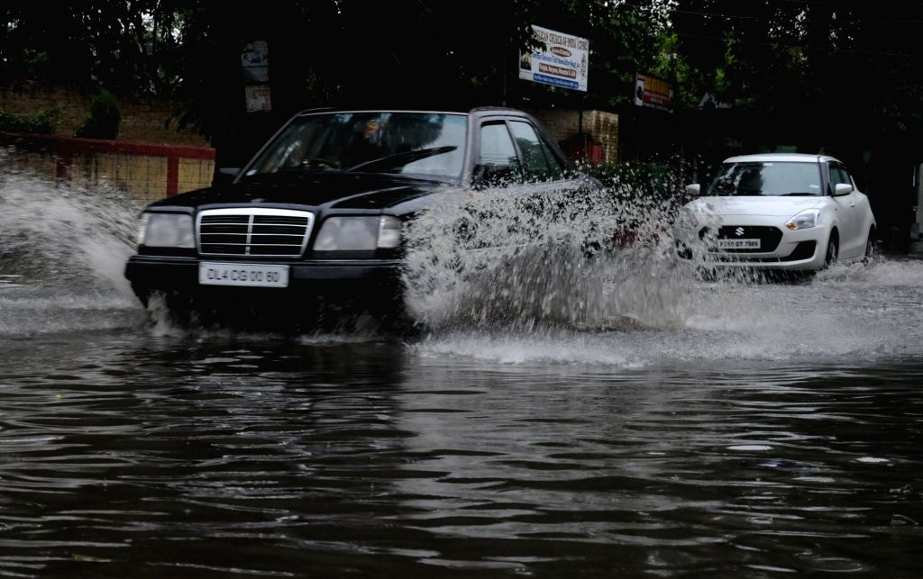 Vehicles wade through a water-logged road after heavy rains, in Amritsar on July 25, 2019.