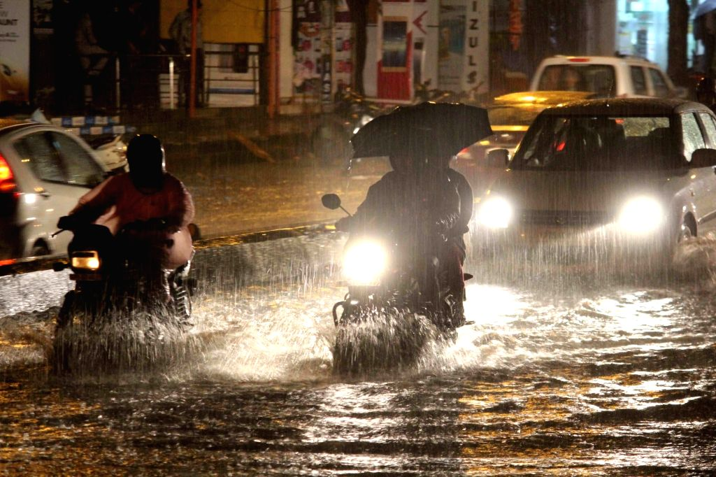Vehicles wade through a water-logged road during rains, in Hyderabad on July 25, 2019.