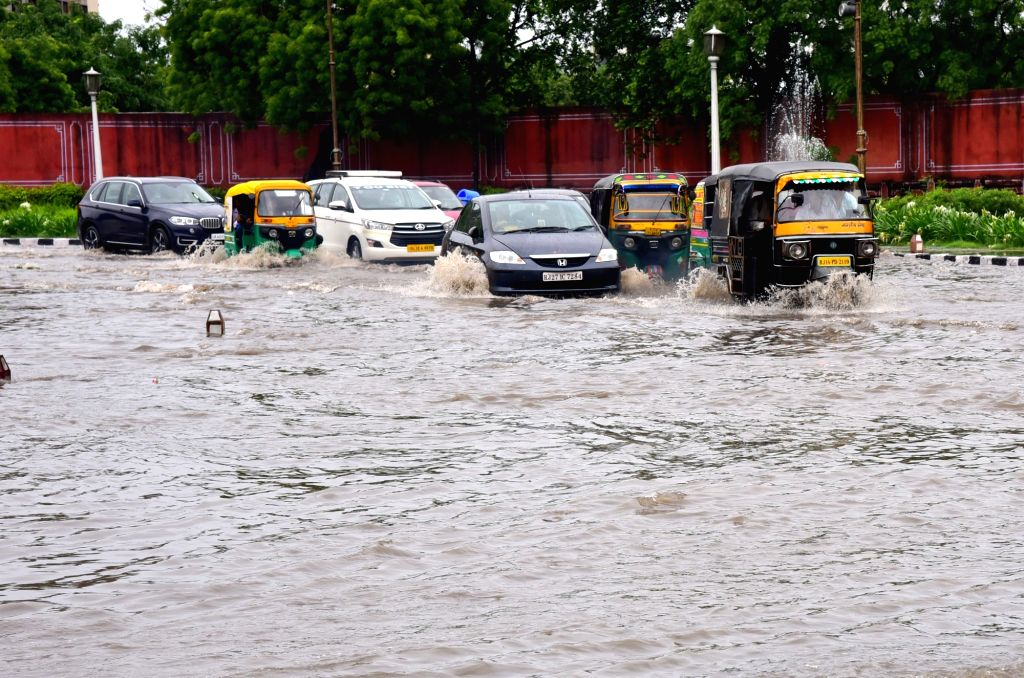 Vehicles wade through a water-logged street during rains, in Jaipur on Aug 15, 2019.