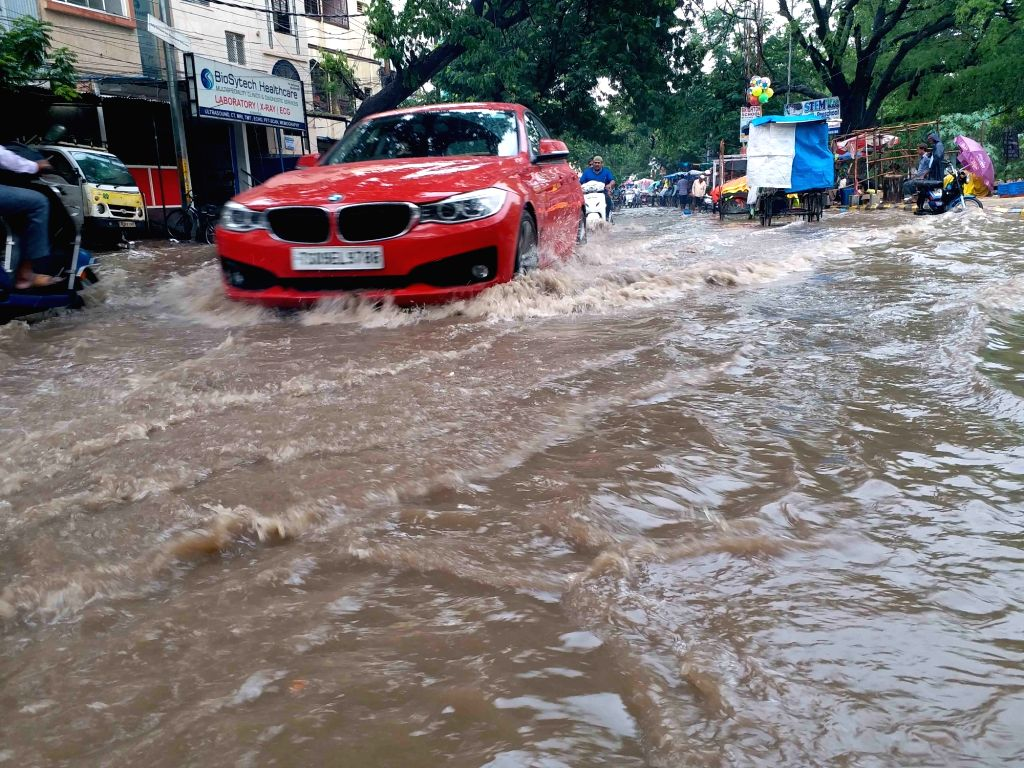 Vehicles wade through a water-logged street after heavy rains, in Hyderabad on July 16, 2019.
