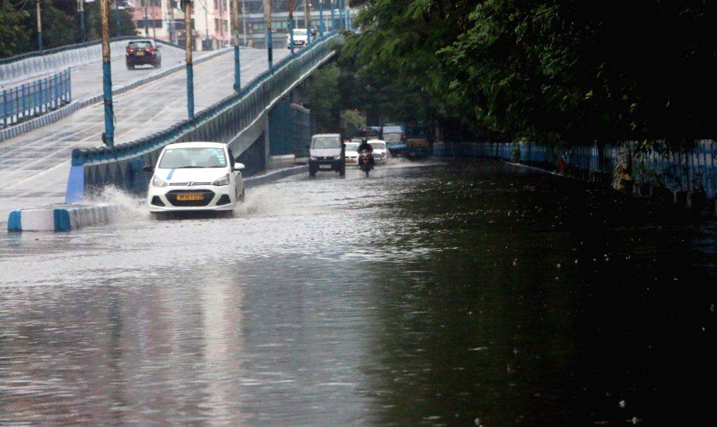 Vehicles wade through a water-logged street after heavy rains in Kolkata, on Oct 9, 2019.