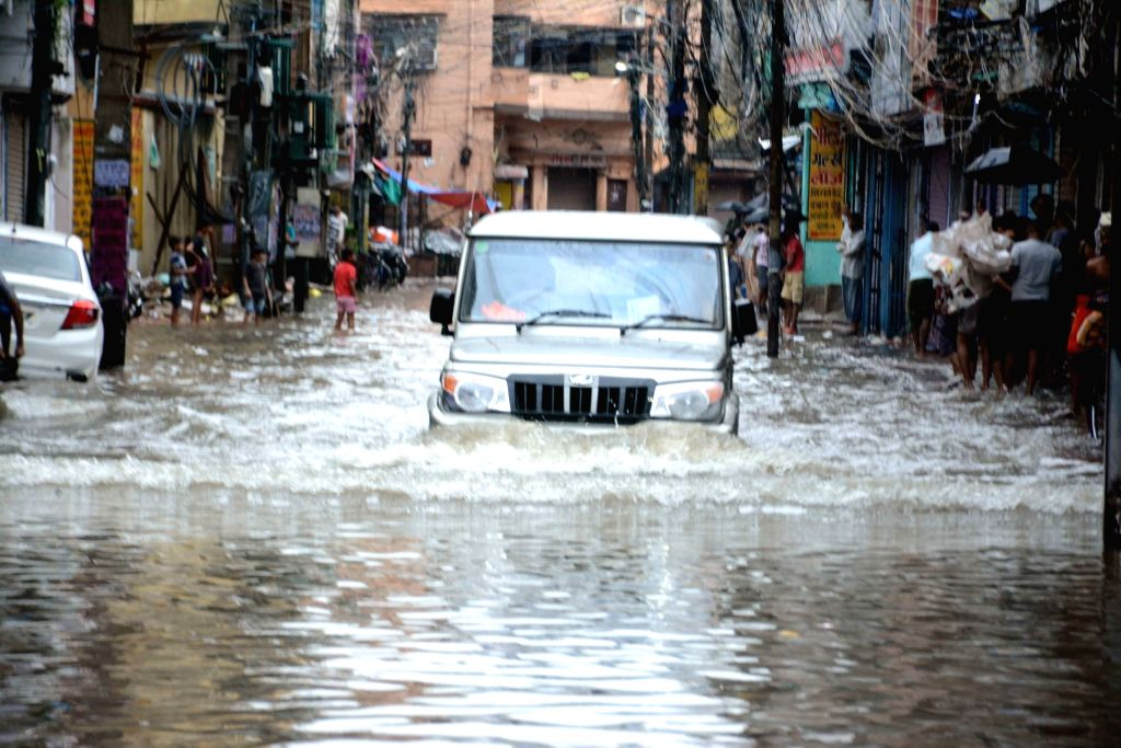 Vehicles wade through waterlogged streets during floods in Patna, on 29 Sep, 2019.
