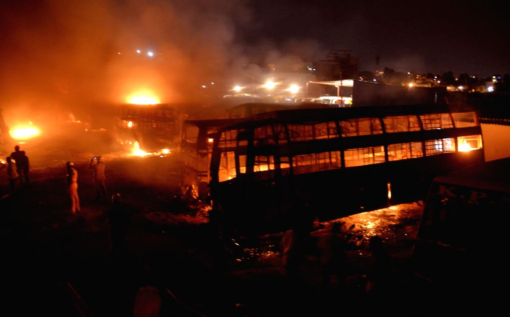 Vehicles with Tamil Nadu registration numbers being torched by protesters in the bus depot at Dwaraka Nagar; in Bengaluru on Sept 12, 2016.