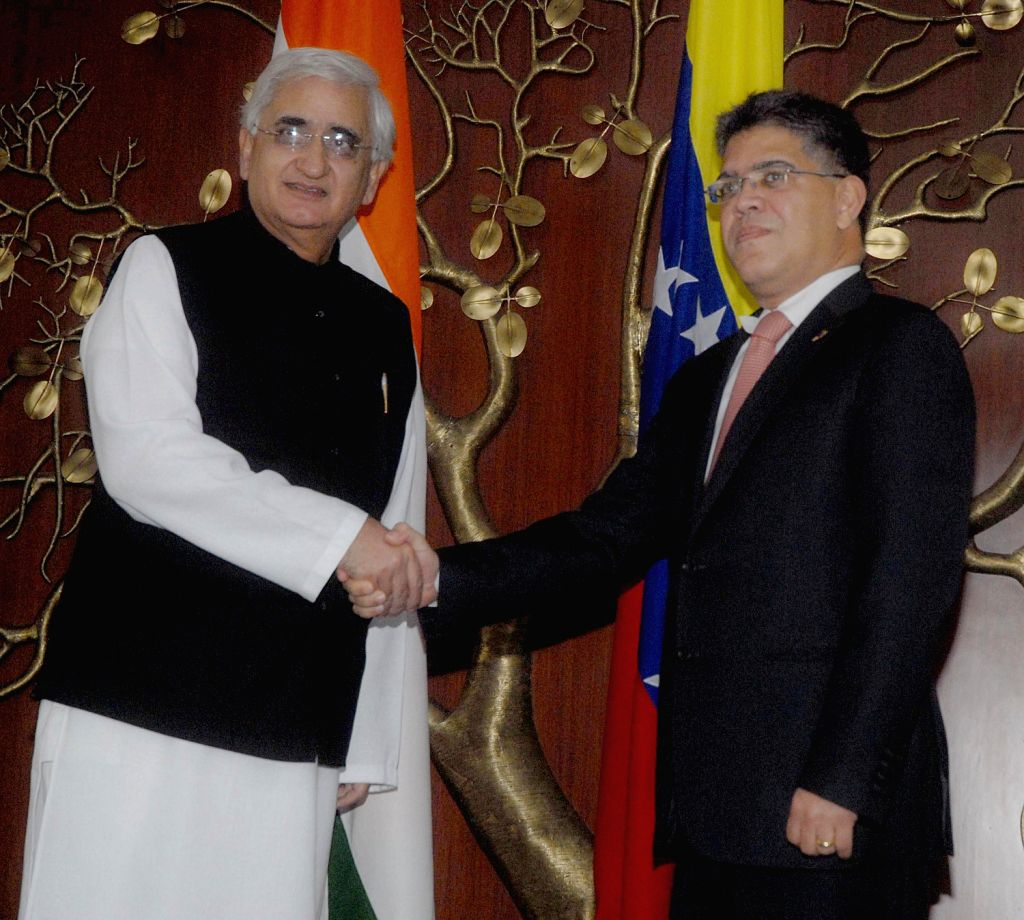 Venezuela's Minister of Popular Power for Foreign Relations Elias Jaua Milano shakes hands with External Affairs Minister Salman Kurshid  during a meeting in New Delhi on Dec.20, 2013.