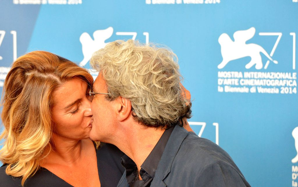 """Director Mario Martone (R) and screenwriter Ippolita di Majo kiss during the photo call for """"Il giovane favoloso"""" which is selected for the main ..."""
