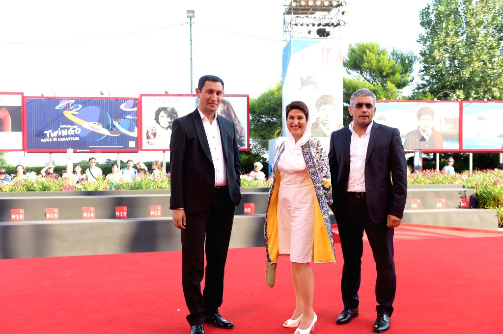 """Azerbaijani director Elchin Musaoglu (R) and actress Fatemeh Motamed Arya (C) pose on the red carpet for """"NABAT"""", which is selected in the Orizzonti unit, . - Fatemeh Motamed Arya"""