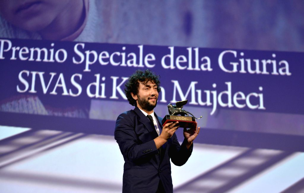 "Turkish director Kaan Mujdeci poses with his trophy of the Special Jury Prize for his movie ""Sivas"" during the awards ceremony at the 71st Venice Film ..."
