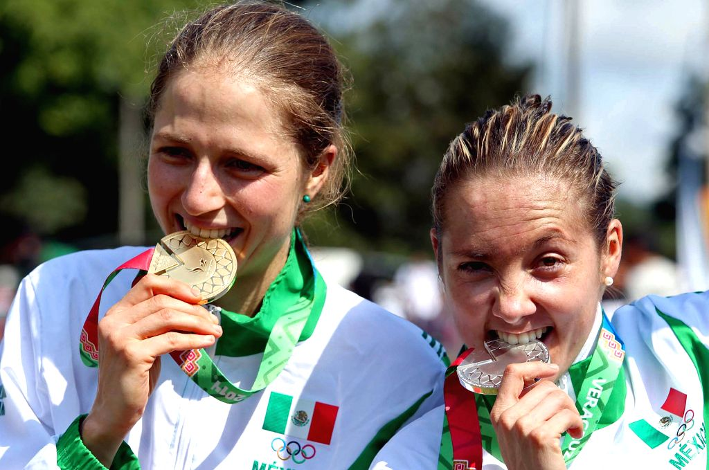 Mexico's cyclists Daniela Campusano Chavez (L) and Laura Lorenza Morfin pose during the awarding ceremony of the mountain cycling competition in the 2014 Veracruz Central American and ...