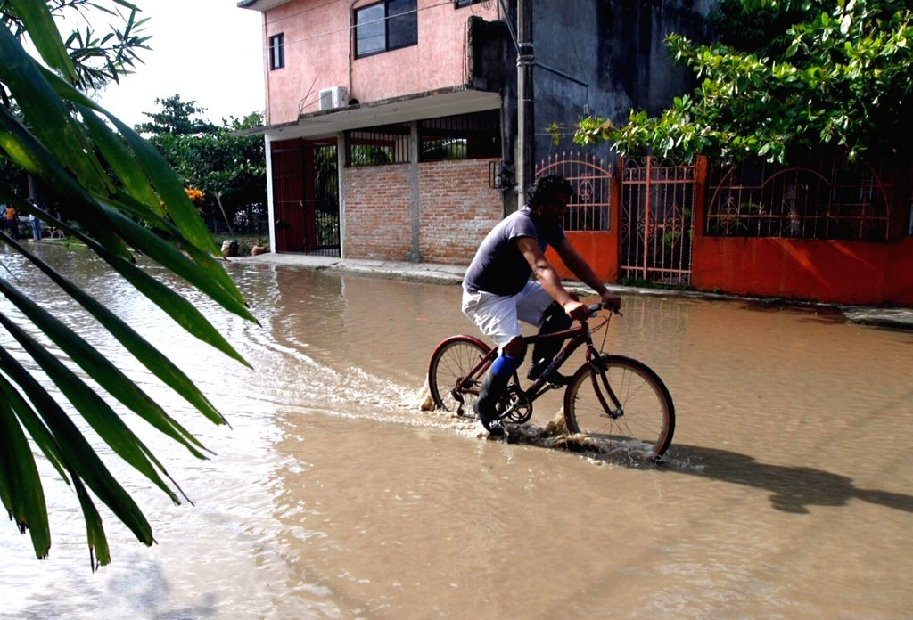 VERACRUZ, Sept. 10, 2017 - A man rides a bicycle in a flooded street in Tecolutla, Veracruz state, Mexico, Sept. 9, 2017. Tropical storm Katia left at least two people dead in Mexico's Gulf Coast ...
