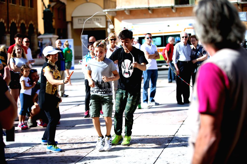VERONA (ITALY), Sept. 18, 2016 A boy (C) plays fancy rope skipping together with a Chinese performer (R) during Tocati in Verona of Italy, on Sept. 17, 2016. Artists from different places ...