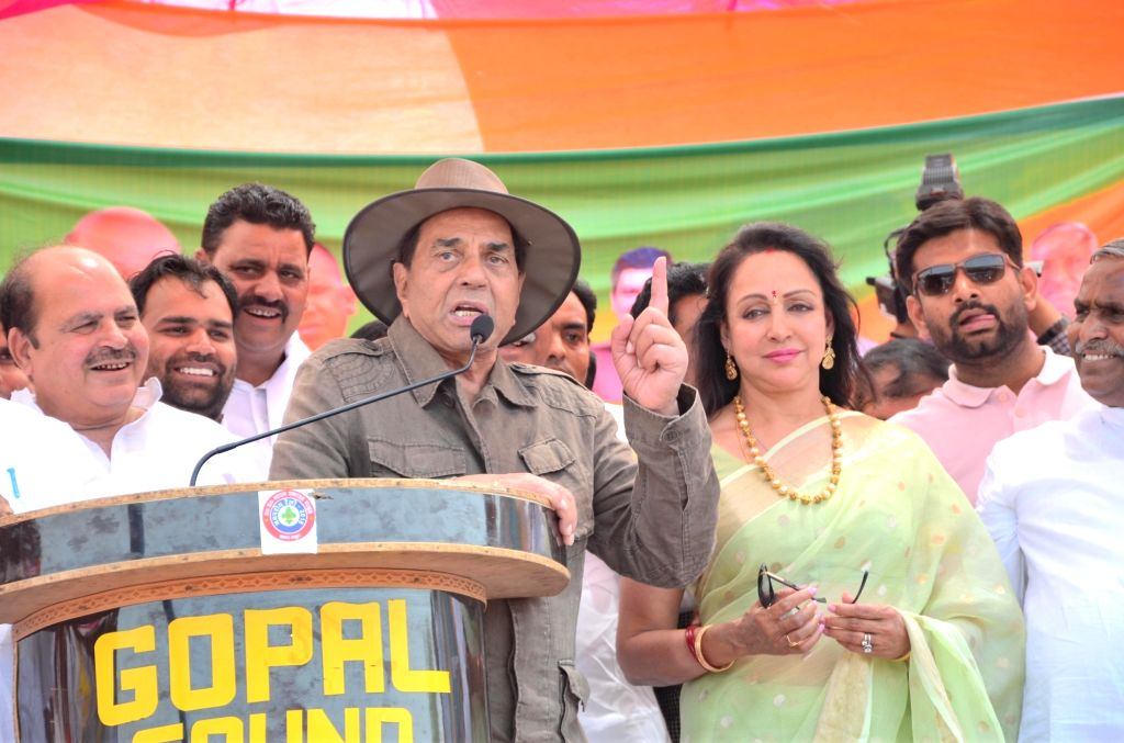 Veteran actor Dharmendra addresses during a campaign on behalf of his wife, actress and BJP's MP Hema Malini in Mathura, on April 14, 2019. - Dharmendra and Hema Malini