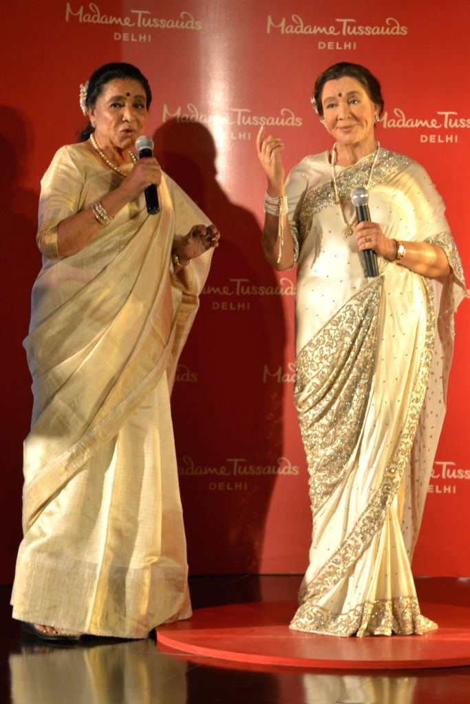 Veteran singer Asha Bhosle with her wax statue that was unveiled at the Madame Tussauds museum in New Delhi on Oct 3, 2017. - Asha Bhosle