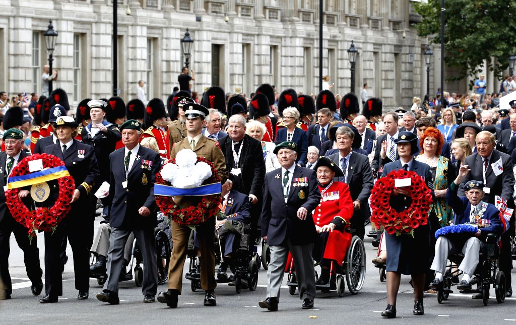 Veterans and their families pass by the Whitehall in central London as they take part in a parade from Horse Guards Parade to Westminster Abbey after a service of ...