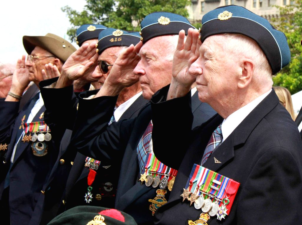 Veterans attend a memorial event at the National War Memorial to mark the 70th anniversary of Victory over Japan Day in Ottawa, capital of Canada, Aug.15, 2015. ...