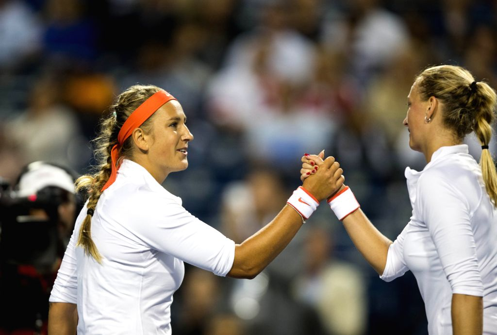 Victoria Azarenka (L) of Belarus shakes hands with Petra Kvitova of the Czech Republic during the women's singles second round match at the 2015 Rogers Cup in ...