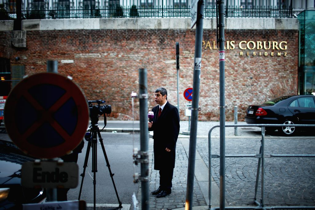 A journalist works outside Palais Coburg, the venue of nuclear talks in Vienna, Austria, Nov. 23, 2014. The world's major powers and Iran are racing against time to reach a deal over Tehran's