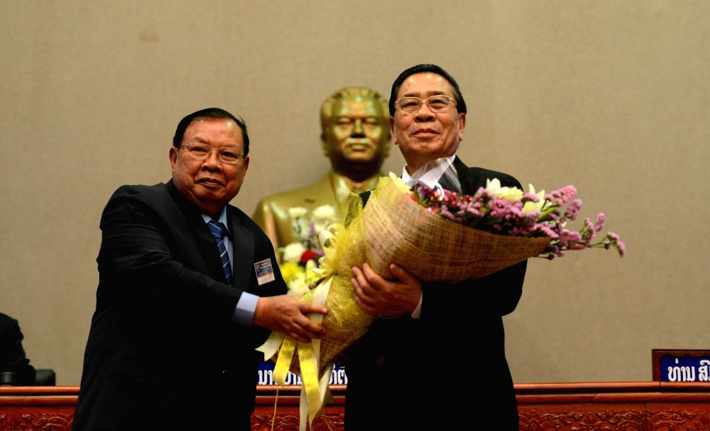 VIENTIANE, April 20, 2016 - Newly elected Lao President Bounnhang Vorachit (L) presents a bouquet of flowers to former Lao President Choummaly Sayasone during the First Session of the eighth Lao ...