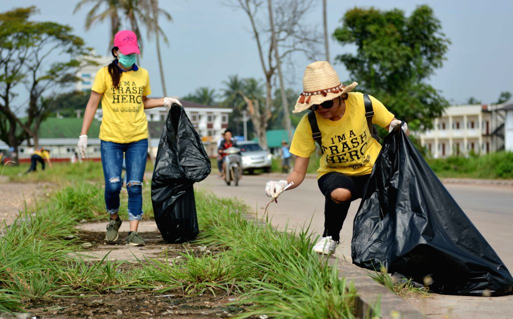 VIENTIANE, Sept. 15, 2018 - Volunteers collect garbage along the street to mark the World Cleanup Day in Vientiane, capital of Laos, on Sept. 15, 2018.