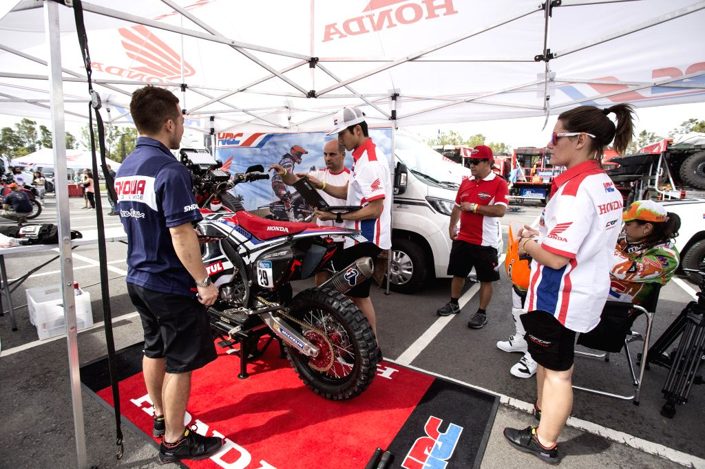 Mechanicians work with a motorcycle that will compete in the Dakar Rally 2015 at Tecnopolis in the town of Villa Martelli, 10km from the city of Buenos Aires,