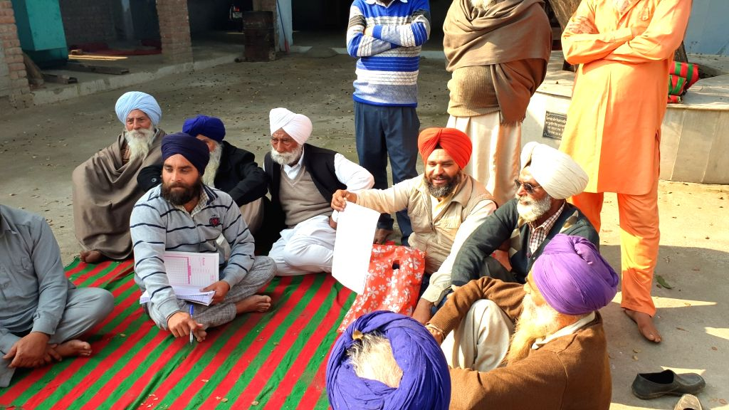 Villagers discussing the land acquisition for the Kartarpur Corridor project  in Pakhoke village in Dera Baba Nanak area of Punjab's Gurdaspur district.