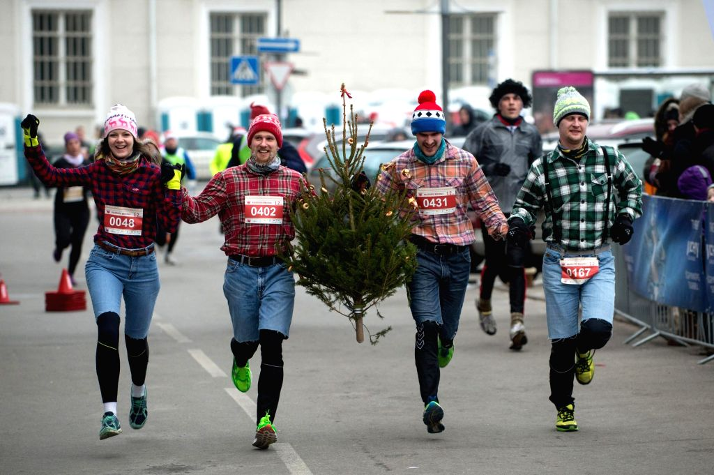 People take part in the race with a Christmas tree in Vilnius, Lithuania, Dec. 28, 2014. The Christmas race in Lithuania this year has events of 12km, 6km, and a ...