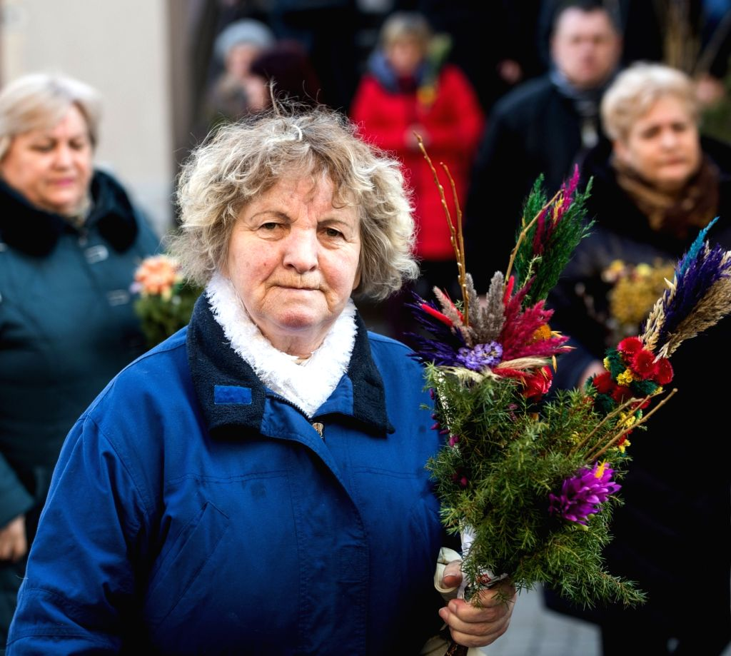 VILNIUS, March 25, 2018 - A woman holds palm products to celebrate the Palm Sunday in Vilnius, Lithuania, on March 25, 2018. Palm Sunday is a Christian feast that falls on the Sunday before Easter ...