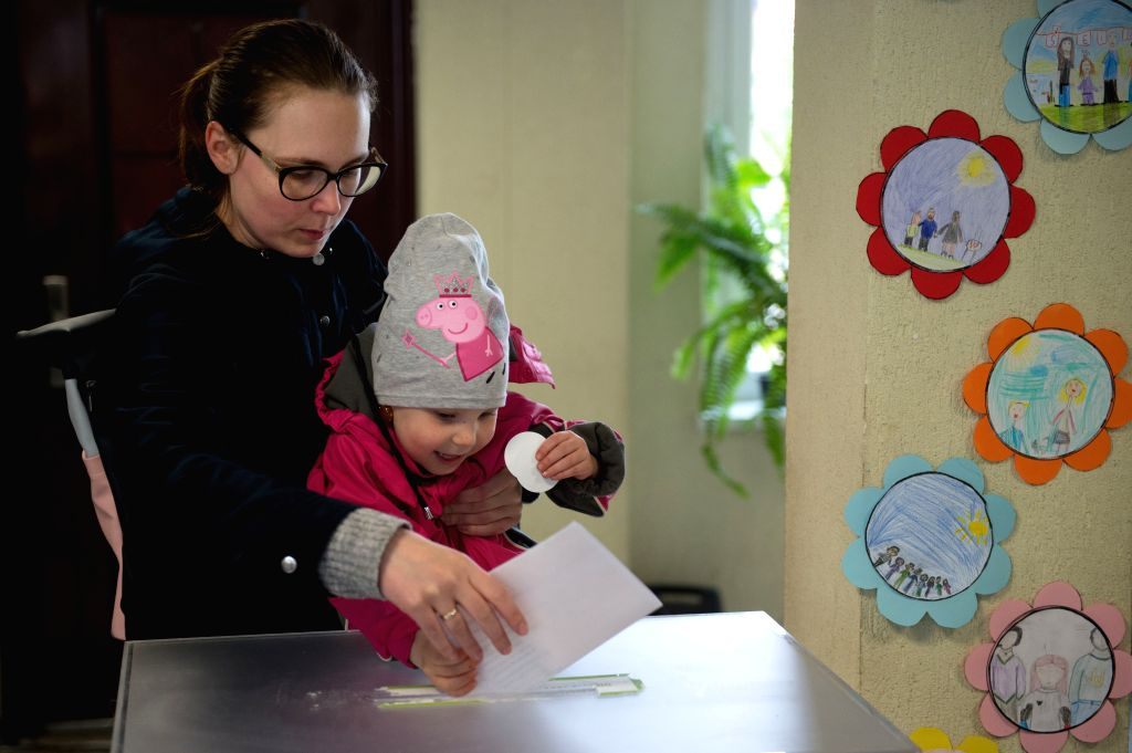 VILNIUS, May 12, 2019 - A child casts a vote for her mother at a polling station in Vilnius, Lithuania, on May 12, 2019. The presidential election and two referendums kicked off in Lithuania Sunday ... - Saulius Skvernelis