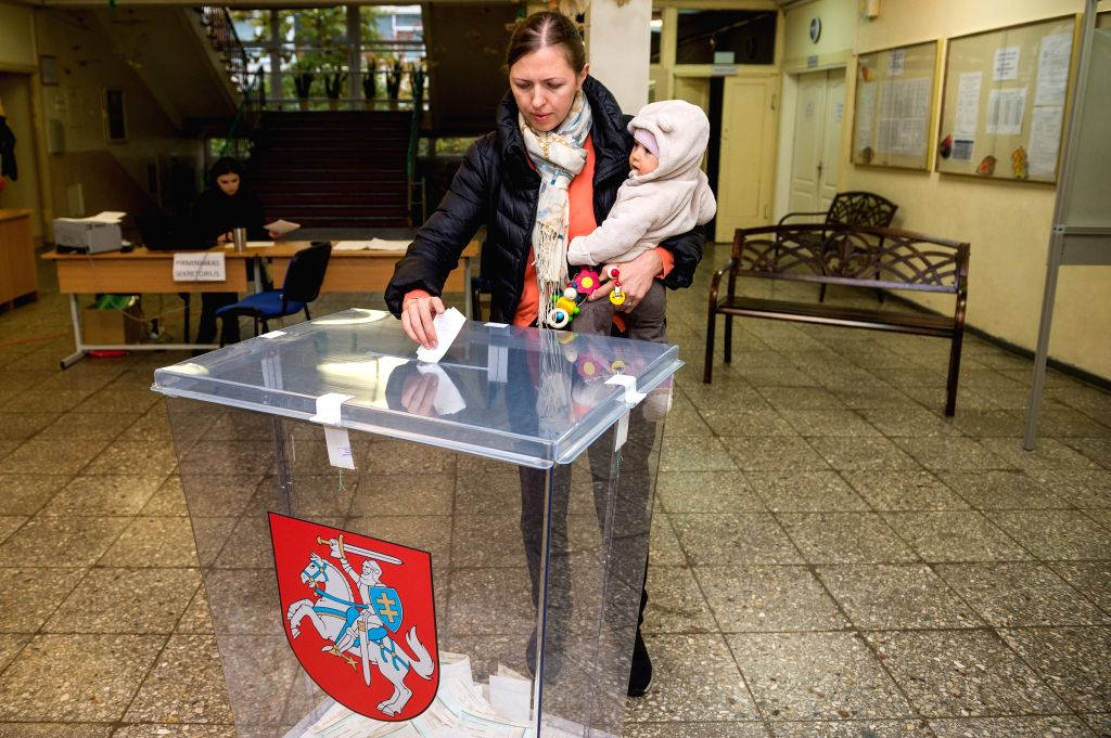 VILNIUS, Oct. 23, 2016 - A voter casts her ballot in a polling station for the parliament election in Vilnius, Lithuania, Oct. 23, 2016. Lithuania is holding the second round of parliamentary ...