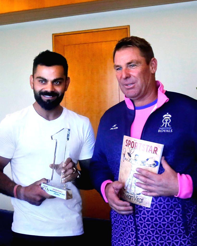 Virat Kohli receives the Sportstar's Sportsman of the Year award by former Australian cricketer Shane Warne. - Virat Kohli