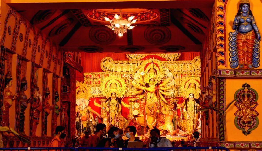 Visitors at a community puja pandal at Ekdalia Evergreen during Durga puja celebrations, at Nabani in Kolkata on Oct 25, 2020.