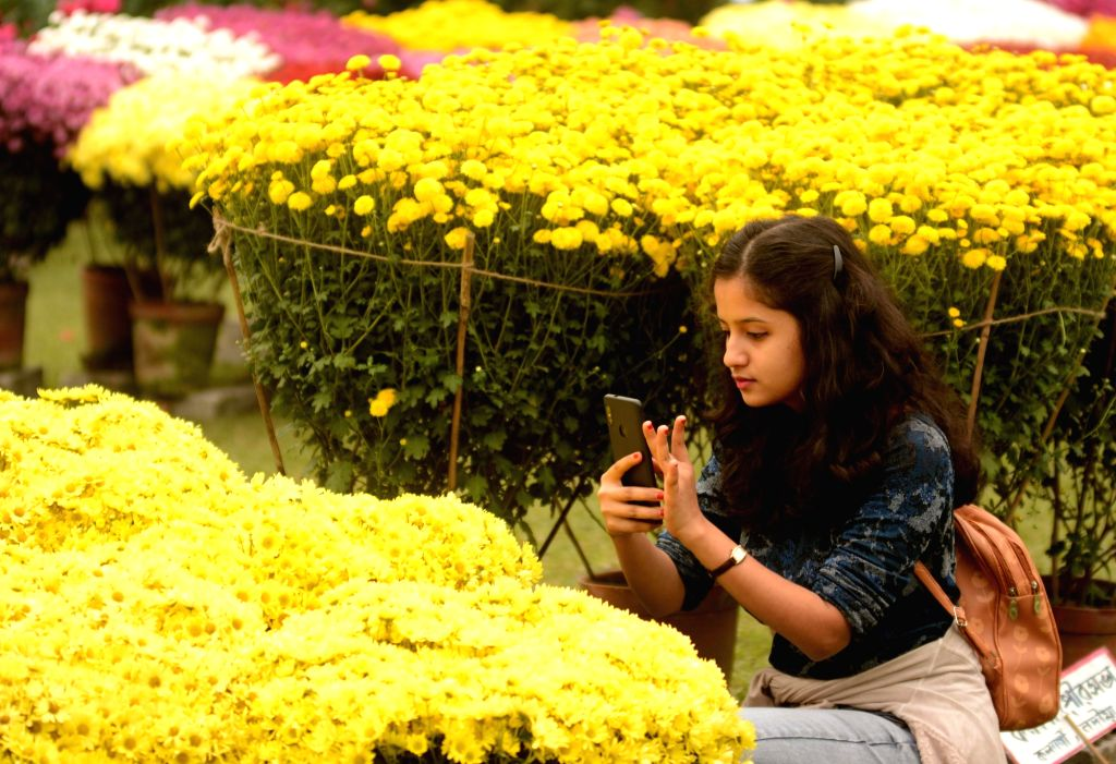 Visitors busy clicking pictures during the Flower Show 2020 at Alipur Horticultural Society of India in Kolkata on Jan 9, 2020.