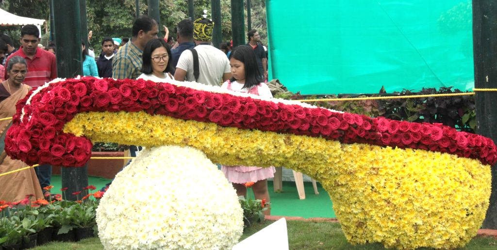 Visitors have a look at a musical instrument made up of flowers on display at the Lalbagh Botanical Garden which is all decked up for Annual Flower Show that will be a part of Independence ...