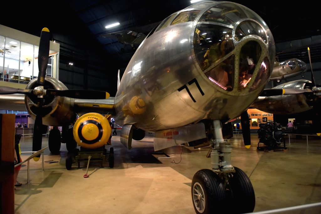 """Visitors look at a demilitarized atom bomb, nicknamed """"Fat Man"""" (L Lower, Yellow), and the Bockscar B-29 bomber at the National Museum of the United States ..."""