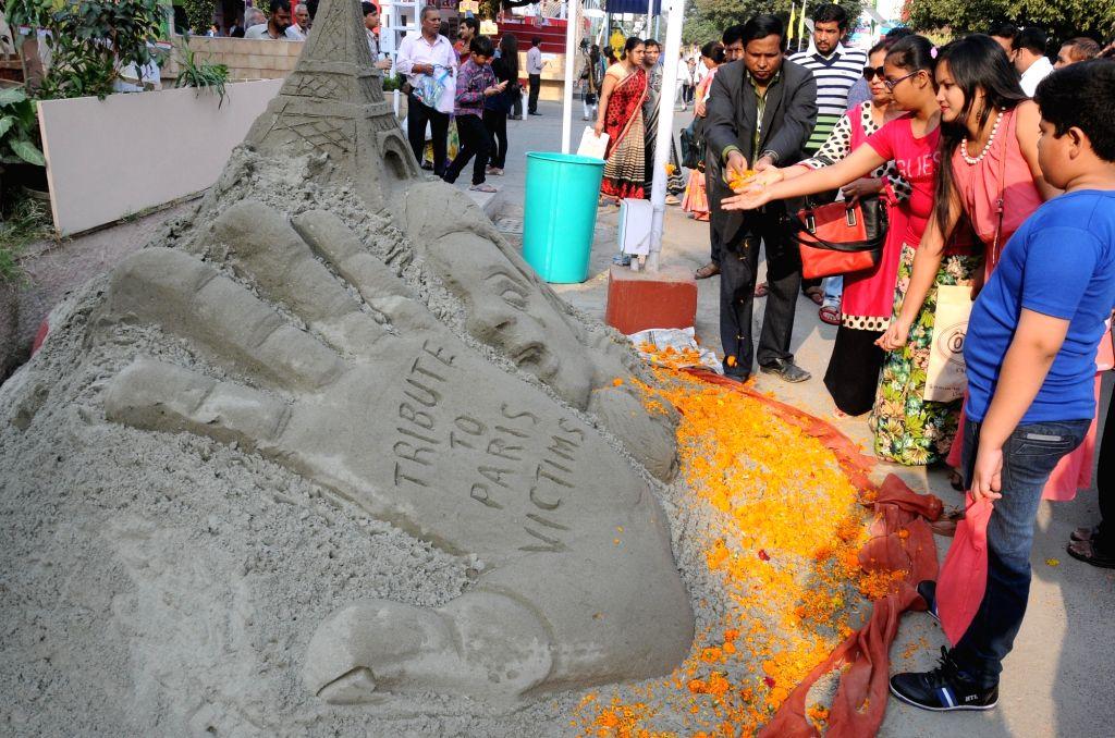 Visitors pay tributes to the terror attack in Paris through a sand art at India International Trade Fair (IITF) -2015 at Pragati Maidan in New Delhi on Nov 15, 2015.