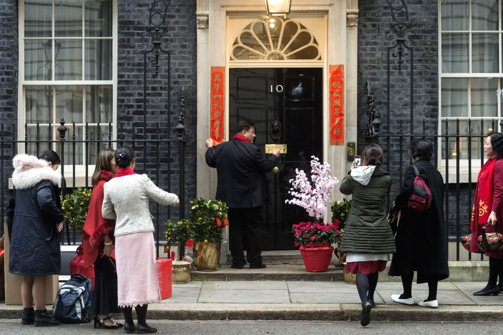 Visitors take photos of couplets in celebration of the Chinese Lunar New Year outside 10 Downing Street in London, Britain, Jan. 24, 2020.