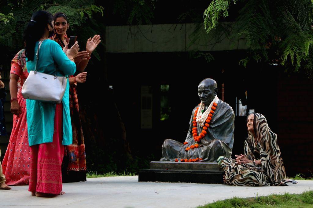 Visitors take selfie with the statue of Mahatma Gandhi on the eve of Gandhi jayanti at Gandhi Ashram in Ahmedabad on Friday,October 01,2021