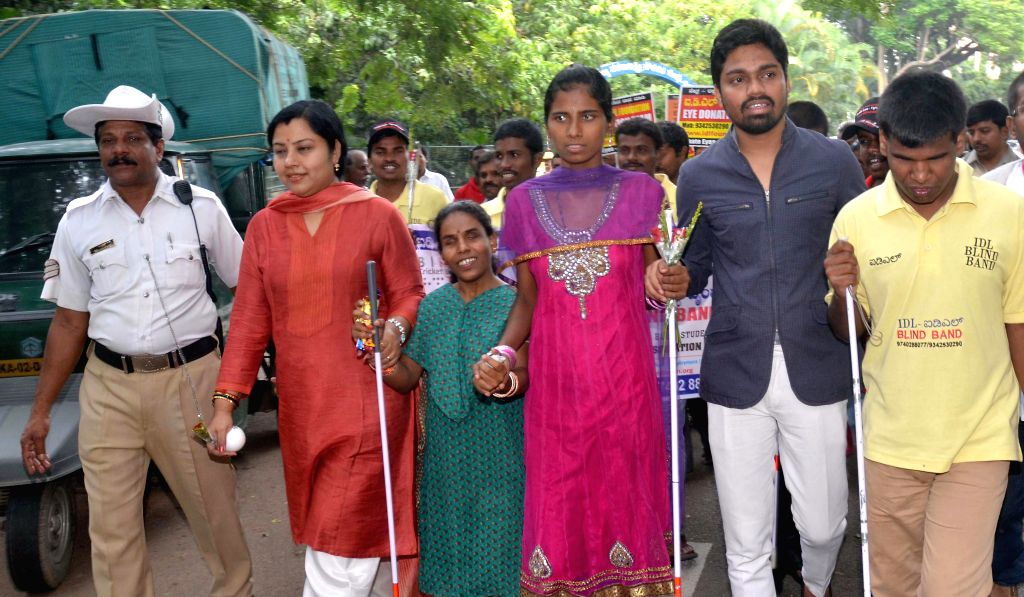 Visually challenged people participate in a walkathon organised on `Friendship Day` in Bangalore on Aug 3, 2014.