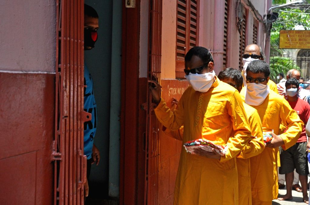Visually impaired moving back to their Ashram after receiving free foods for needy during the extended nationwide lockdown imposed to mitigate the spread of coronavirus, in Kolkata on May 8, ...