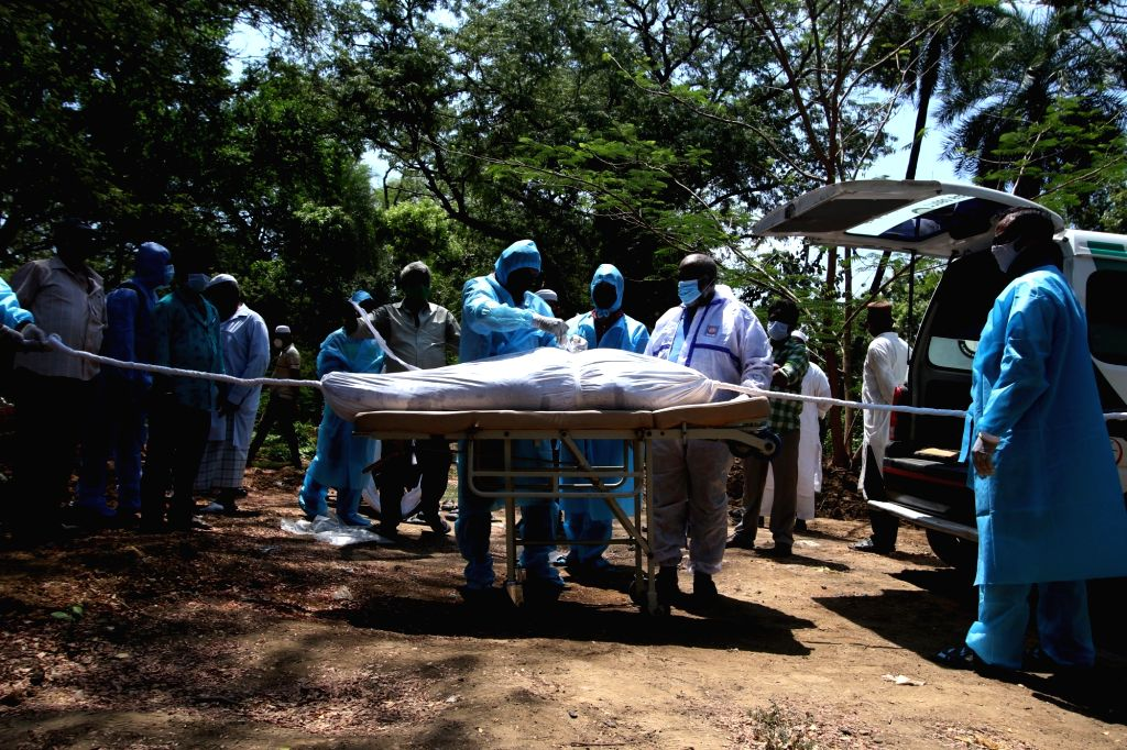 Volunteers and workers bury the body of a COVID-19 victim in Chennai on Saturday June 16, 2021.