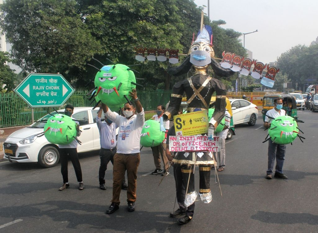 Volunteers display the mascot of a joint awareness initiative on COVID-19 and pollution launched by the New Delhi District Magistrate, urging people to wear masks and save themselves from ...