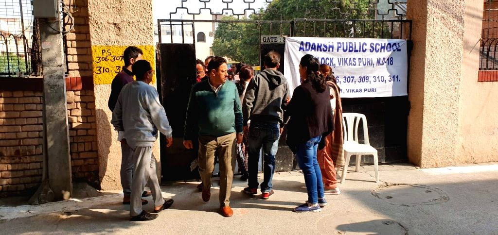Voters arrive to cast their votes for the Delhi Assembly elections 2020, at Adarsh Public school in Delhi's Vikas Puri on Feb 8, 2020.