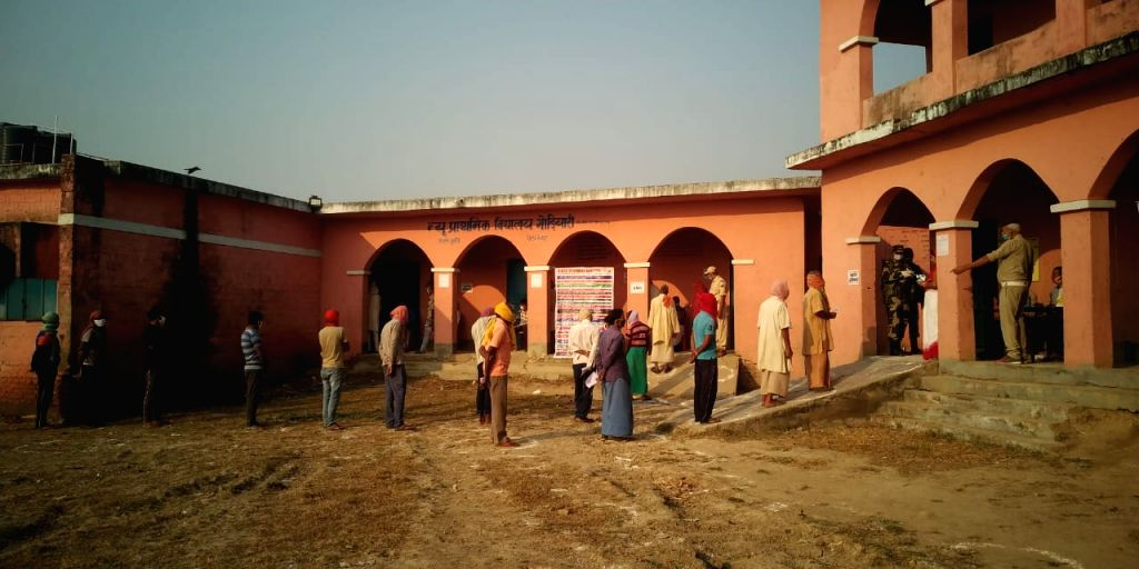 Voters follow social distancing norms as a precautionary measure against COVID-19 as they queue up to cast their votes for the first phase of Bihar Assembly elections, at a polling station in ...