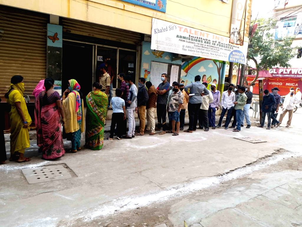 Voters queue up outside a polling station to cast their votes for Greater Hyderabad Municipal Corporation (GHMC) elections, on Dec 1, 2020.