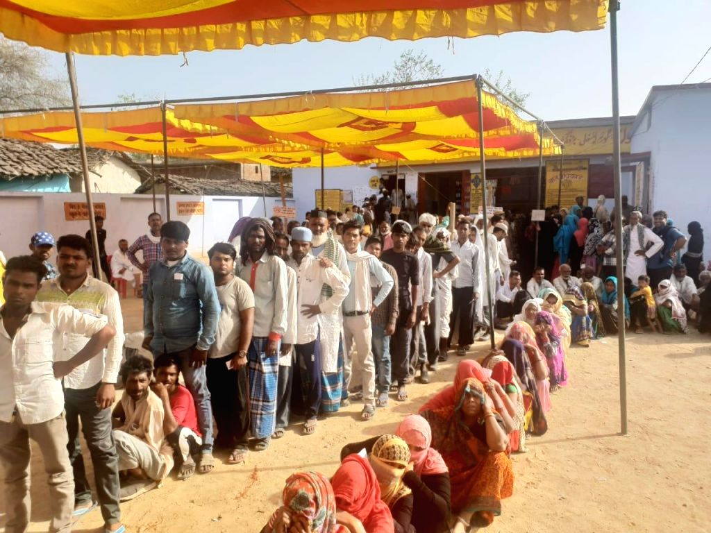 Voters queue up to cast their votes for the fourth phase of 2019 Lok Sabha elections at a polling station in Uttar Pradesh's Banda on April 29, 2019.