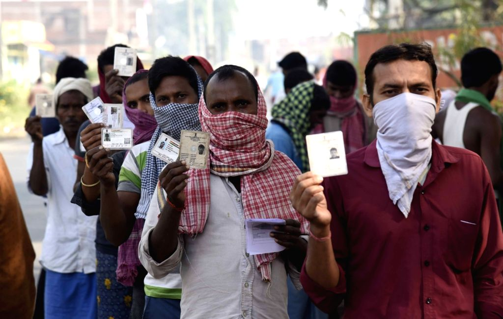 Voters queue up to cast their votes for the first phase of Bihar Assembly elections, at Paliganj in Patna district on Oct 28, 2020.