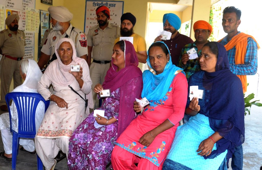 Voters show their identity cards as they wait for their turn to cast their votes during re-polling at the polling station number 123 of Amritsar parliamentary constituency after the ...