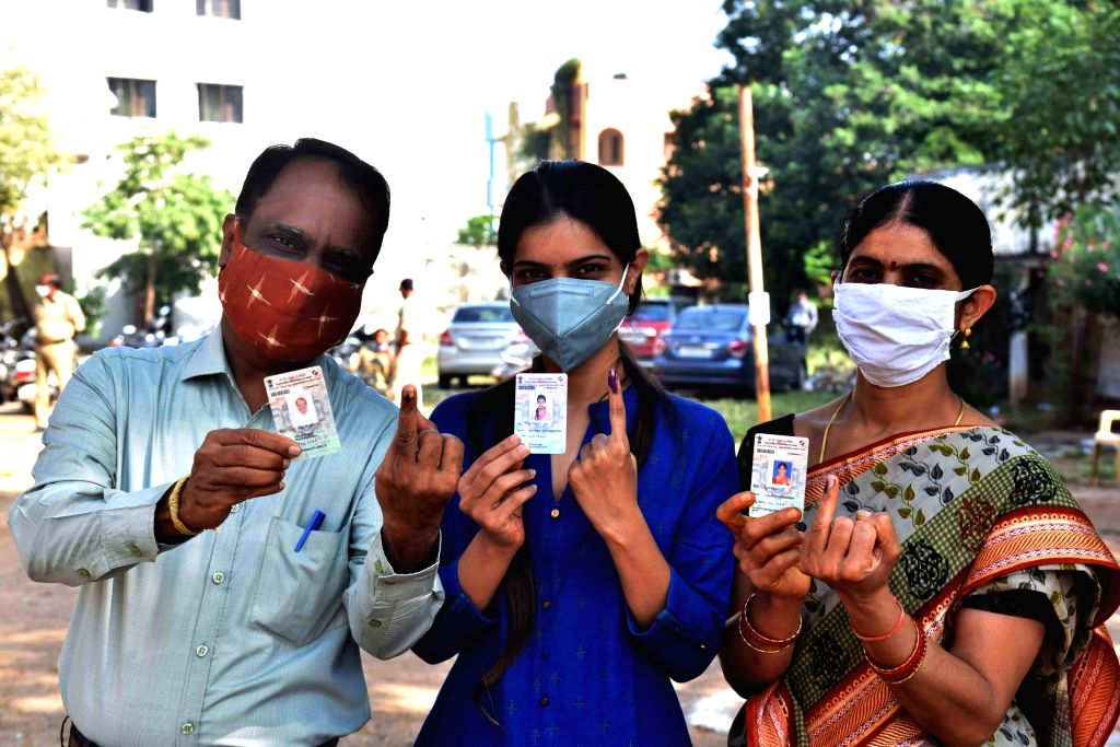 Voters show their inked fingers and Voter IDs after casting their votes for Greater Hyderabad Municipal Corporation (GHMC) elections, on Dec 1, 2020.