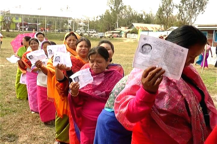 Voters show their voter ID cards as they wait in a queue to cast their vote at a polling booth during the first phase of Manipur Legislative Assembly polls in Churachandpur district of ...