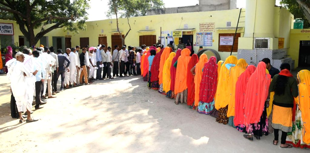 Voters wait in a queue to cast their vote for Rajasthan Assembly elections at a polling booth at Mundia in Newai Tehsil in Tonk District of Rajasthan on Dec 7, 2018.